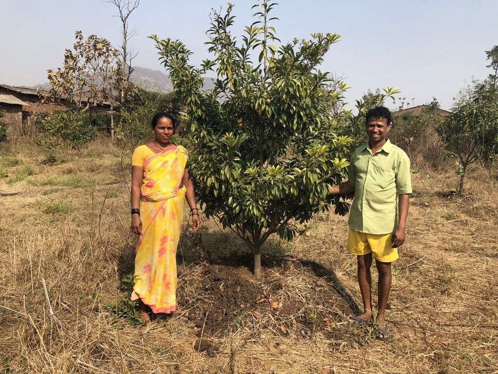 Sudhakar and his wife Sangita proudly posing by one of their fruit trees in 2018